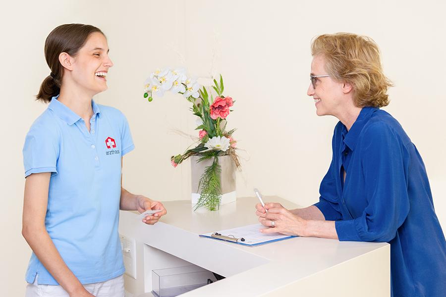 MPA spricht mit Patientin am Empfang in Arztpraxis