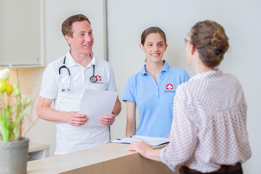 Patientin wird von Arzt und MPA am Empfang begrüsst
