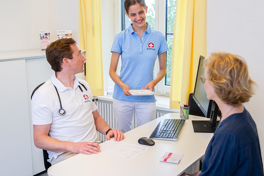 Arzt und MPA sprechen mit Patientin im Behandlungszimmer