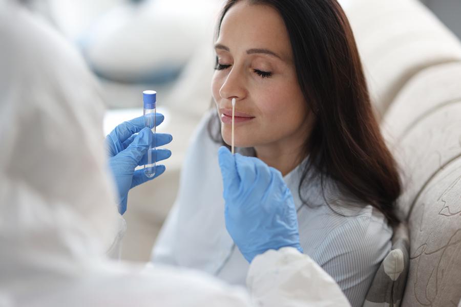 MPA in Schutzausrüstung macht einen Abstrich in der Nase der Patientin