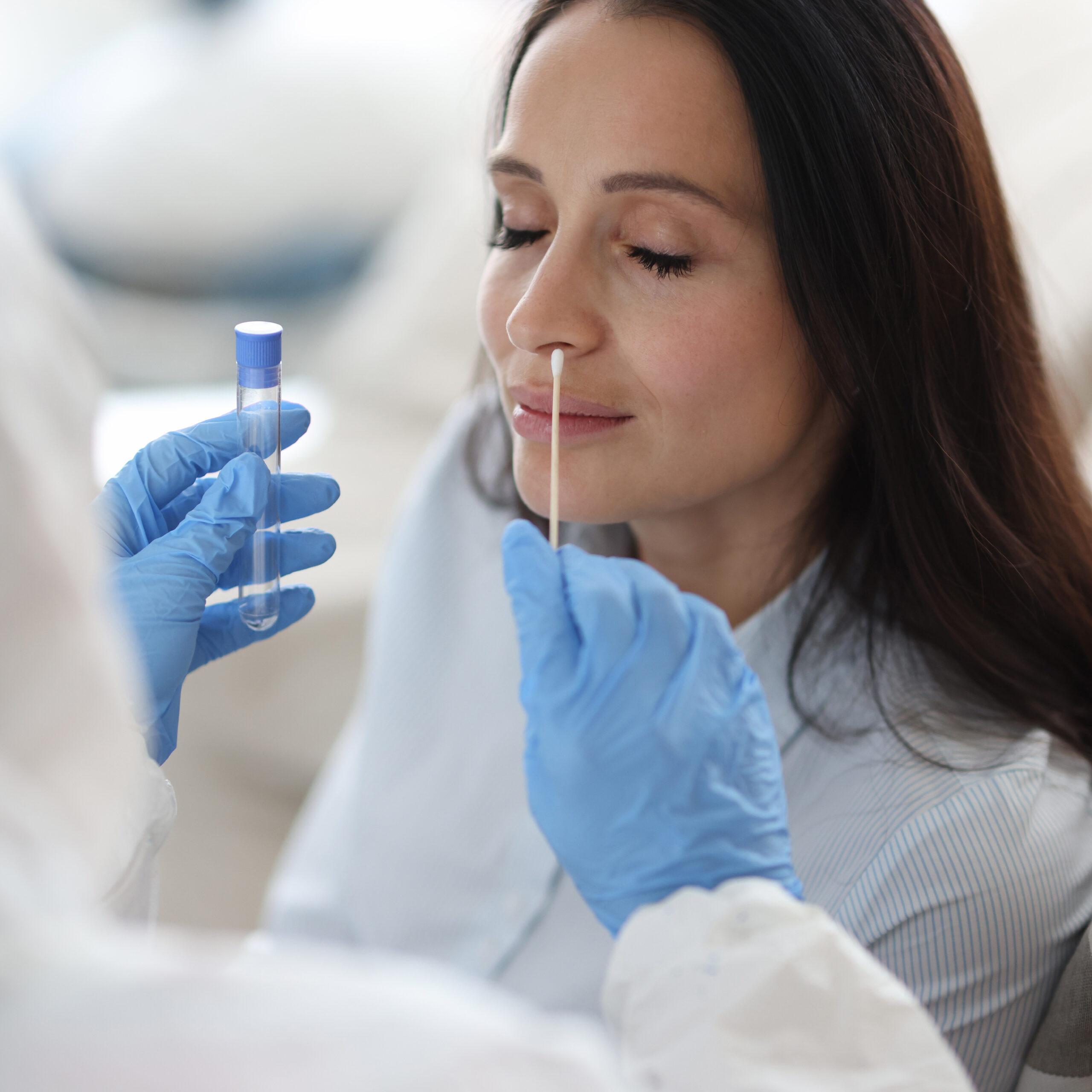 MPA in Schutzausrüstung macht einen Abstrich in der Nase der Patientin. Labortest für Coronavirus Konzept.