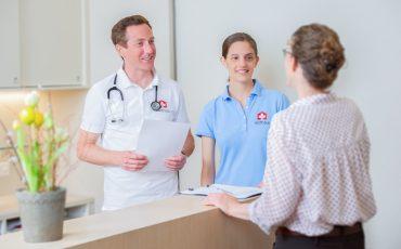 Arzt, MPA und Patientin sprechen am Empfang in Arztpraxis