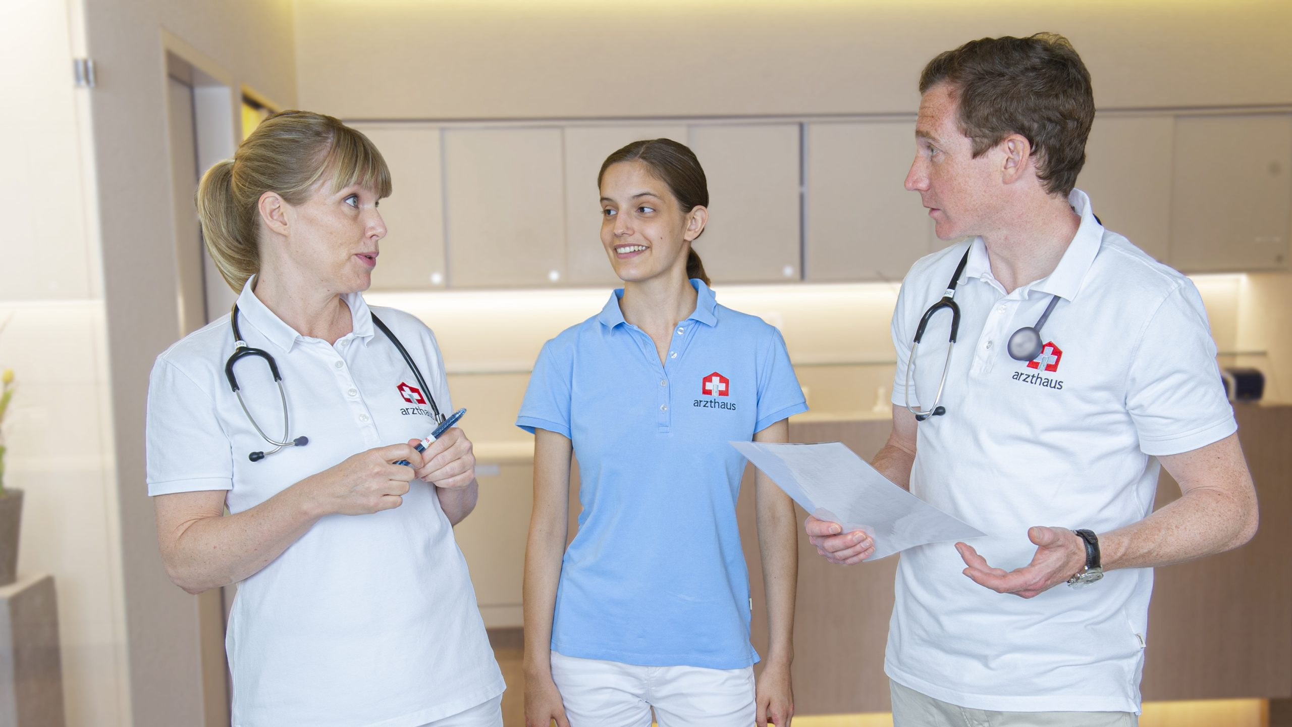 Zwei Ärzte und MPA, die zusammen sprechen